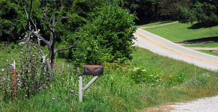 Backroad View in the Ozarks. Rusty metal mailbox sits on wooden posts. Highway climbs mountain on the backroads of the Ozark Mountains in Arkansas stock photo