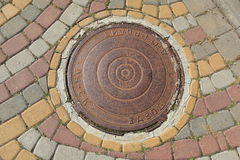Rusty metal manhole cover in a street Royalty Free Stock Photo