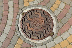 Rusty metal manhole cover in a street Stock Images