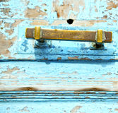 Rusty metal nail dirty stripped paint in the blue wood door and Stock Photo