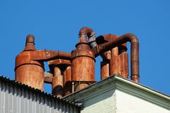 Rusty metal pipes and chimneys on a roof Royalty Free Stock Photo