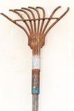 Rusty metal rake. Vintage rusty metal rake for gardening on white concrete wall Stock Photos
