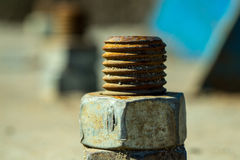 Rusty metal screws. Rusty screws metal nuts screwed with corroded bolts on steel beam on grunge blurred background Royalty Free Stock Photo