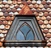 Rusty metal shingle roofing with attic window closeup Royalty Free Stock Photography