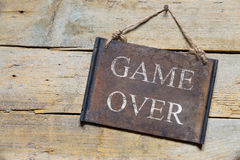Rusty metal sign on wooden table, text game over Stock Image