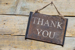 Rusty metal sign on wooden table, text thank you. Greetings and gratitude Royalty Free Stock Images
