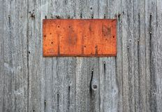 Rusty metal sign on wooden wall. Royalty Free Stock Images