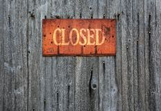 Rusty metal sign with the word closed. Rusty metal sign on wooden wall with the word Closed Royalty Free Stock Photo