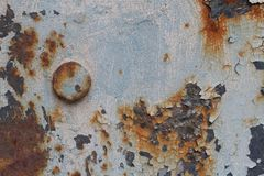 Rusty metal surface with cracked paint and a large bolt Royalty Free Stock Photo