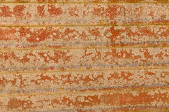Rusty metal surface with grooves and burst paint. A rusty metallic surface showing the effects of weathering Royalty Free Stock Photos