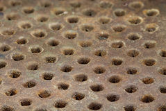 Rusty metal surface with round holes arranged in a row Royalty Free Stock Photos