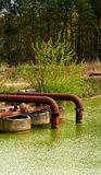 Rusty metall pipes ending in the water. Stock Images