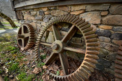Rusty Mill Wheel Gears. Large rusty old mill wheel gears along a stone wall Stock Photo