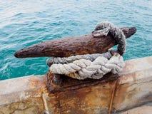 Rusty Mooring Bollard con la cuerda en el embarcadero Imagen de archivo