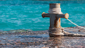 Rusty mooring bollard with ship ropes and  clear turquouse sea ocen water on background.  Stock Photo