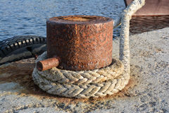 Rusty mooring bollard with ship ropes on dock Royalty Free Stock Image