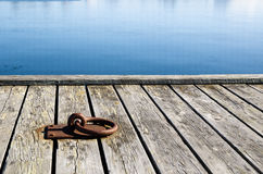 Mooring loop. A rusty mooring loop at a wooden pier in sunlight Royalty Free Stock Photo