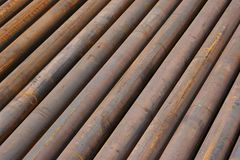 Rusted ms steel pipes diagonally arranged. Rusty MS Steel Pipes kept at a factory for fabrication. useful for textures and backgrounds Stock Photo