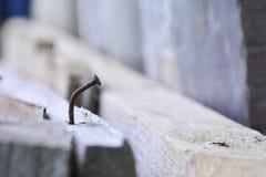 Rusty Nail Curva de un clavo oxidado que se pega fuera del tablero imagenes de archivo