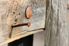 Rusty nail in old wooden construction royalty free stock photography