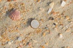 Rusty nickels lying on sand on a sea beach. Rusty nickels lying on the sand on a sea beach stock photo