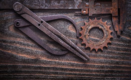 Rusty obsolete measuring calipers with gear wheel on vintage dar Royalty Free Stock Photo