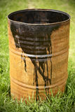 Rusty oil barrel on green grass. Royalty Free Stock Images