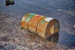 Rusty oil barrel near the shore of the sea Stock Photos