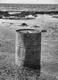 Rusty oil barrel near the shore of the sea Royalty Free Stock Photos