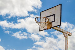 Rusty old basketball board. Against a blue sky with white clouds Stock Image