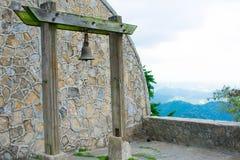 Rusty Old Bell Hanged i mossig träpelare med bakgrund för vägg för stenmodellbåge, Overviewing upptill av en kulle arkivbilder