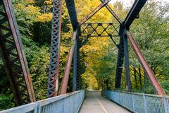 Rusty old bridge. Large metal bridge in maple tree forest in fall Royalty Free Stock Image