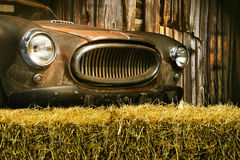 Rusty old car. An old rusty farm car parked outside a wooden barn Stock Photography