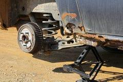 Rusty Old Car Up auf Jack During eine Reifen-Änderung stockfotos