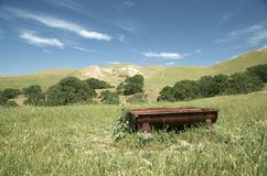 Rusty old cattle water trough near hills. On a sunny day Stock Photo