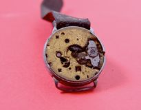 Rusty old clock mechanism on red background. Image of a Stock Images