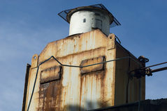 Rusty old cooling unit. Exterior of old rusty cooling unit on refrigeration plant with blue sky background Stock Photo