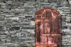 Rusty Old Door On Rock-Wand Stockfotos