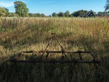 Rusty, old farm equipment. His last resting place. Rusty, old farm equipment, where the grass grows high around it`s last resting place. It was a nice sunny stock images