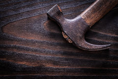 Rusty old-fashioned claw hammer on vintage dark wooden board clo Stock Image