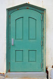 Rusty old green metal door in a white plaster wall Royalty Free Stock Photography