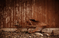A rusty old horse plow in front of a weathered wooden barn wall in brown color tone for a western look. A closeup of the antique rural farming machine made of Stock Photo