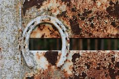 Rusty old horseshoe on trailer. This rusty, old, horseshoe is mounted on a cattle trailer as a decorative accent. background metal rustic texas texture unique royalty free stock images