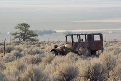 Rusty Old Jalopy Overlooking Sagebrush och Pinyon sörjer öknen i Nevada royaltyfria foton