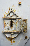 Rusty old keyhole. Old, rusty metal keyhole with small opened door, on a metal gate Royalty Free Stock Images