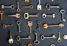 Rusty old keys locks - on dark wooden rustic background. Top view stock photo