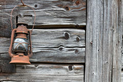 Rusty old lantern on wooden wall. Rusty old lantern hanged on an old wooden wall Royalty Free Stock Image