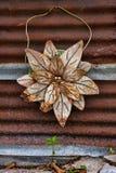 Rusty Old Metal Flower Hanging en una pared galvanizada del metal Fotografía de archivo libre de regalías