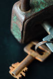 Rusty old metal key and lock on dark background Stock Image