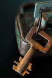 Rusty old metal key and lock on dark background Stock Images